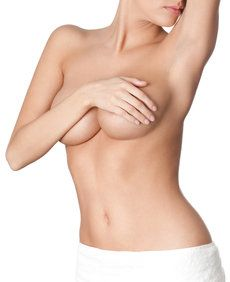 woman covering breasts with her arm