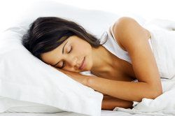 A beautiful woman sleeping peacefully in a white bed with white pillows.