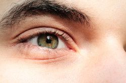 Close up of a man's green eye and eyebrow.