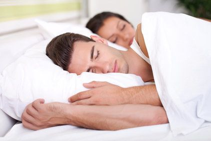 Couple sleeping in a bed with white sheets