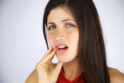 Woman with long brown hair holding tooth in pain