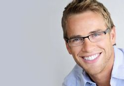 A blonde man wearing half-rimmed glasses smiles brightly.