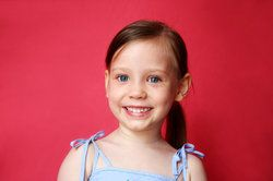 An adorable little girl with a ponytail smiles happily standing in front of a red background.