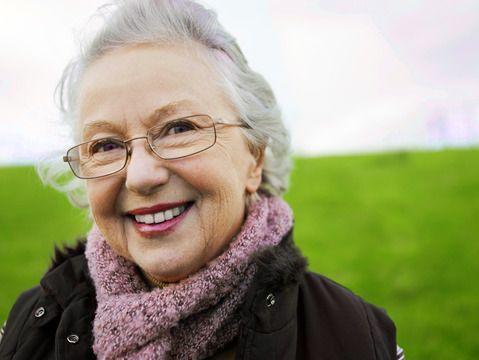 Une femme âgée debout à l'extérieur avec une écharpe rose.