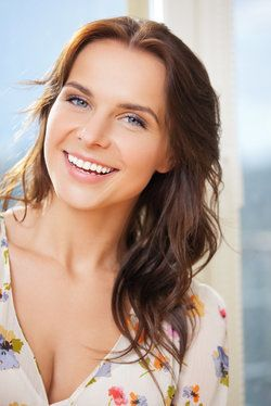 Smiling young woman with brown hair and very straight, white teeth