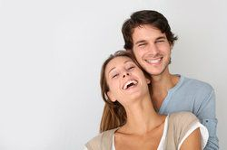 Young couple in an embrace, the woman showing off her healthy smile made complete with an inlay