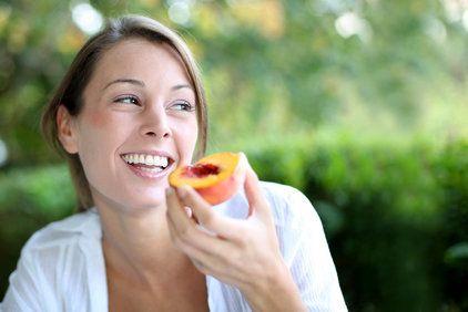 Happy woman eating a peach