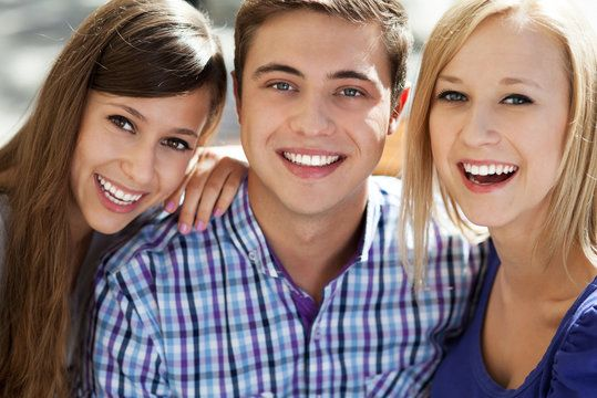 A young boy and two young girls smiling together