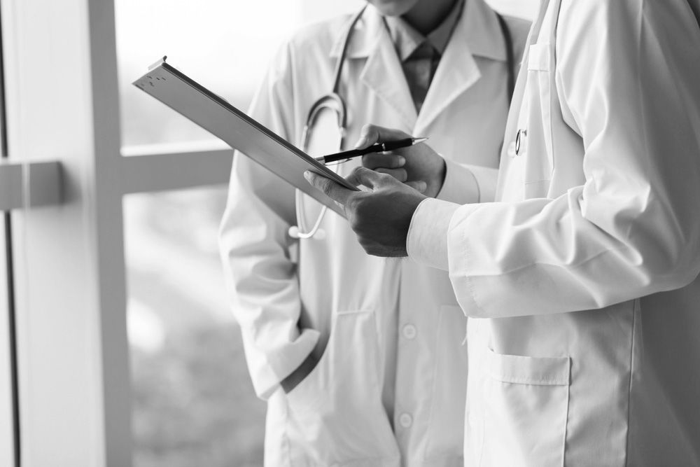 Photo of two people in white doctors coats discussing over a clipboard