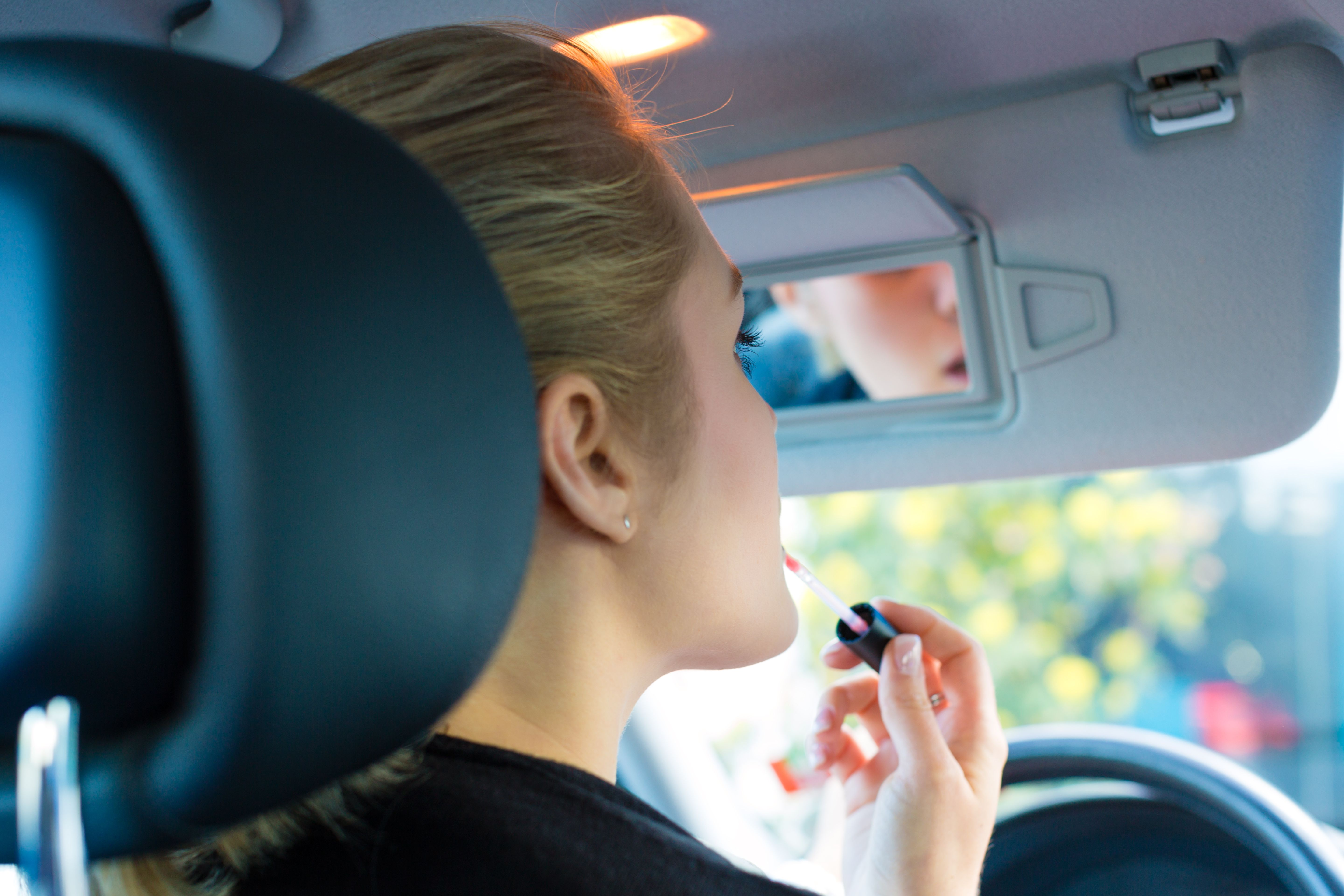Woman applying makeup while driving
