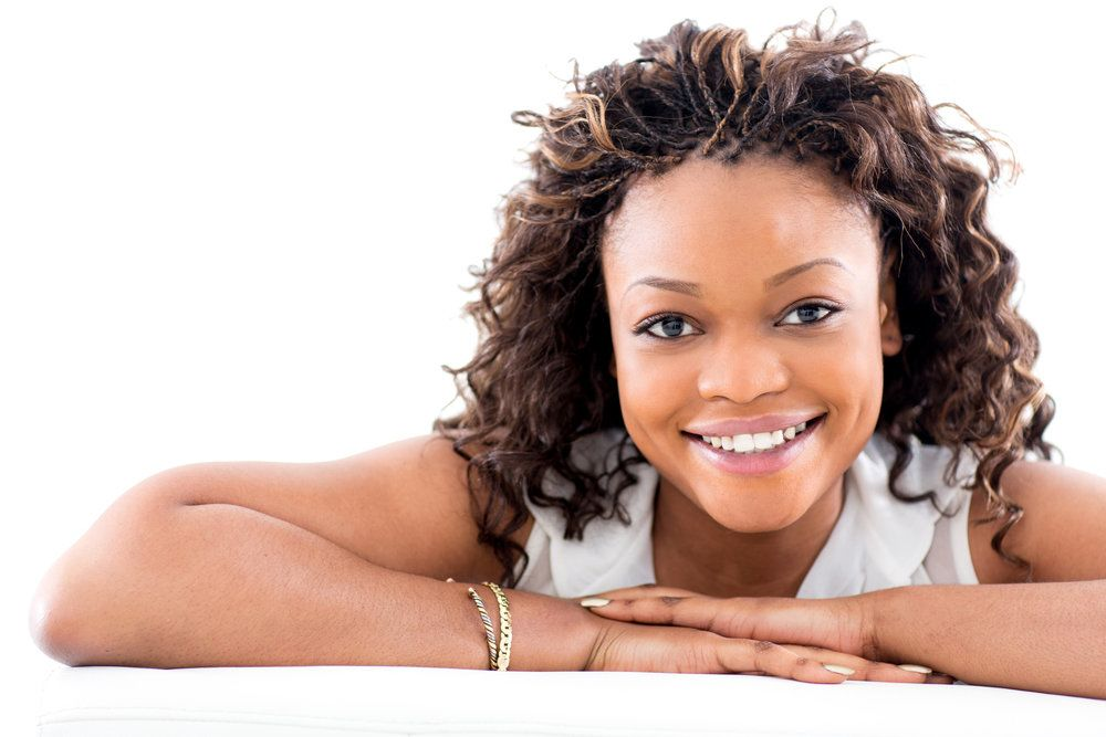 Smiling woman with folded arms and very curly hair