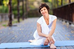 A brunette woman sitting on a yoga mat outdoors