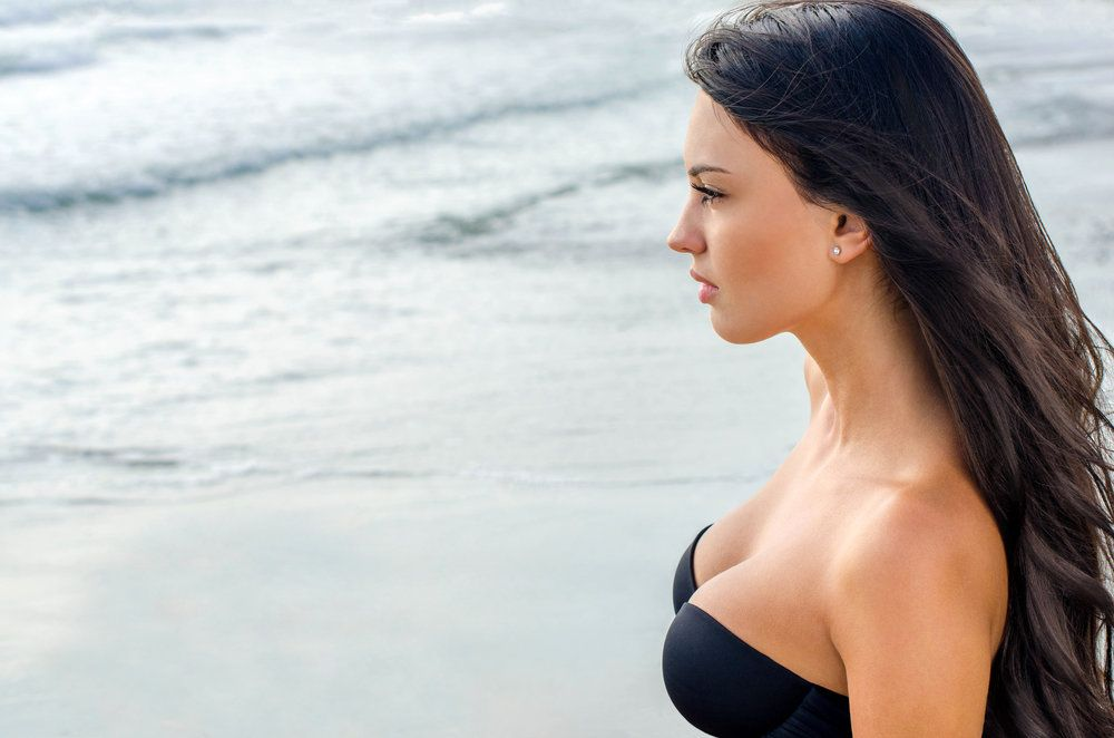 Sexy brunette girl looking at the sea