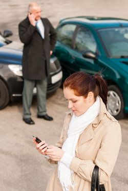 A woman using her phone at the scene of a car accident