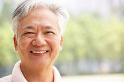 Smiling Asian man with white hair and pink collared shirt