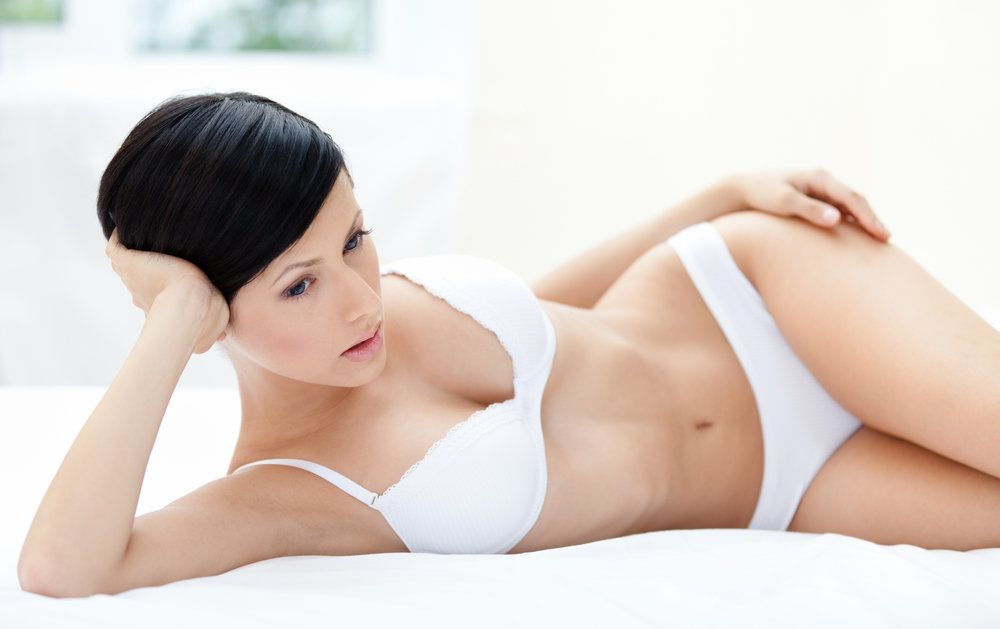 Woman lying in lingerie, her breasts ideally shaped after breast augmentation using the areolar incision technique