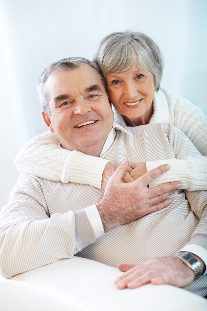 An elderly couple in an embrace, their dental health and heart health both in excellent shape