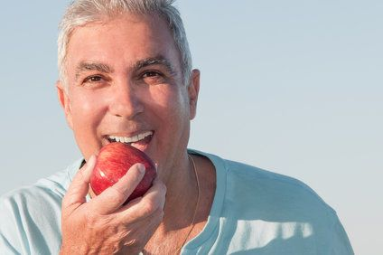 Image of smiling older man with apple