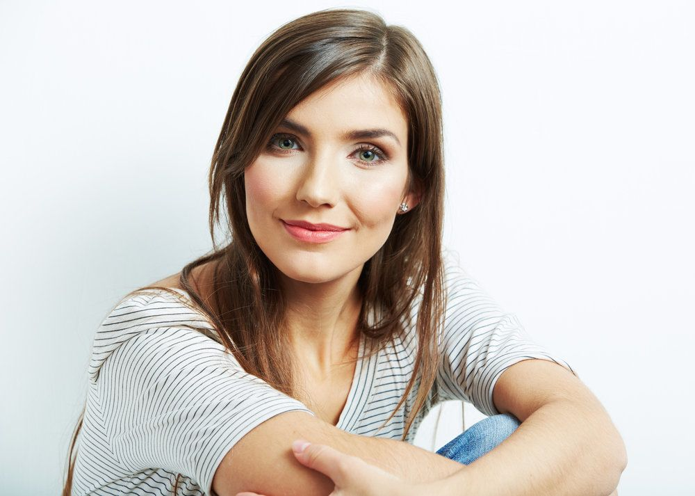 Woman in striped shirt smiling on white backdrop