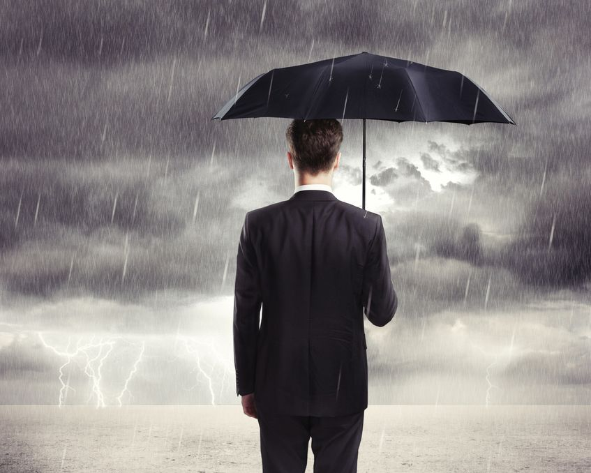 Man in business suit holding umbrella in lightning storm and looking at horizon