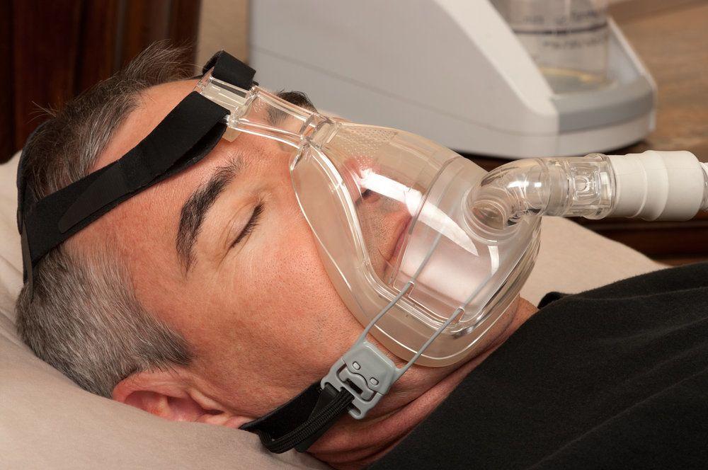 A man wearing a CPAP machine