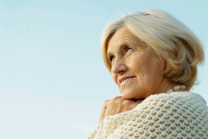 Elderly Caucasian woman looking wistful with hands balled up under chin