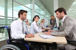 Employer in wheelchair consulting with man over paperwork