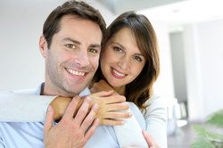 Middle-aged Caucasian couple with beautiful teeth smiling and hugging