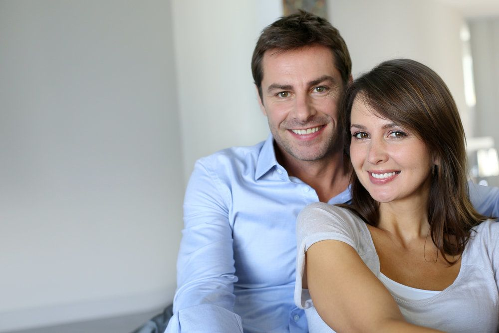 A man and his pregnant wife, who is smiling to reveal her teeth, which are radiant due to excellent dental care during her pregnancy