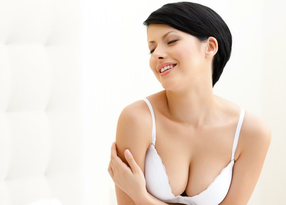 Brunette woman in white bra hugging herself