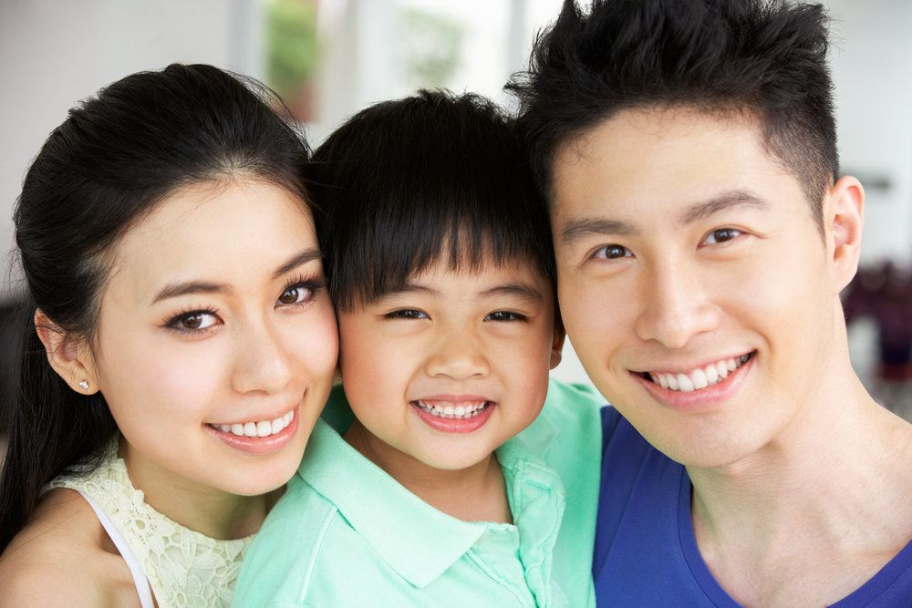 A young family holds one another close while smiling and wearing blue and green shirts.