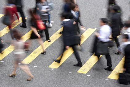 Many pedestrians walking in opposite directions across street