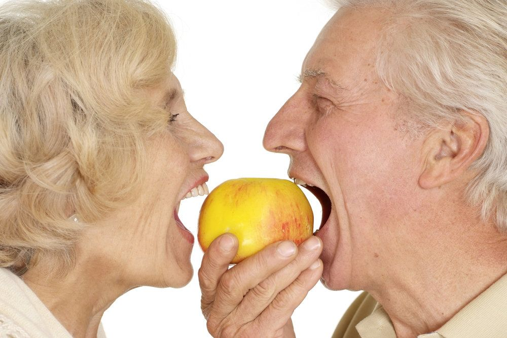 Cost of dentures: older couple enjoying an apple