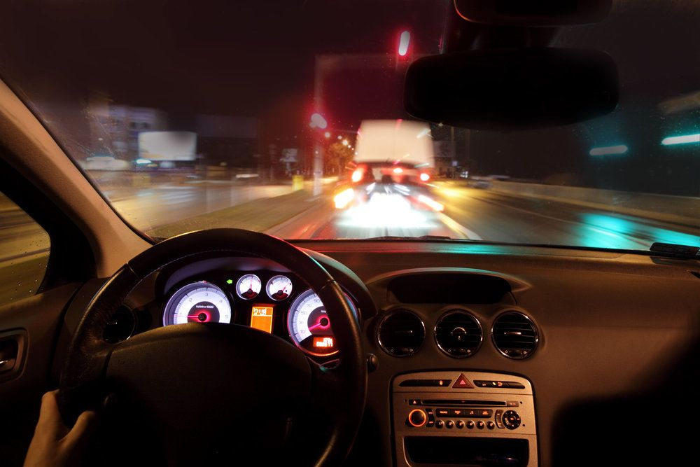 The steering wheel and dashboard of a car being driven at night
