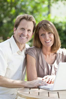 A happy couple using a computer outdoors