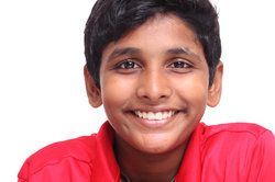 Young boy with straight, healthy teeth after correction of his orthodontic problems