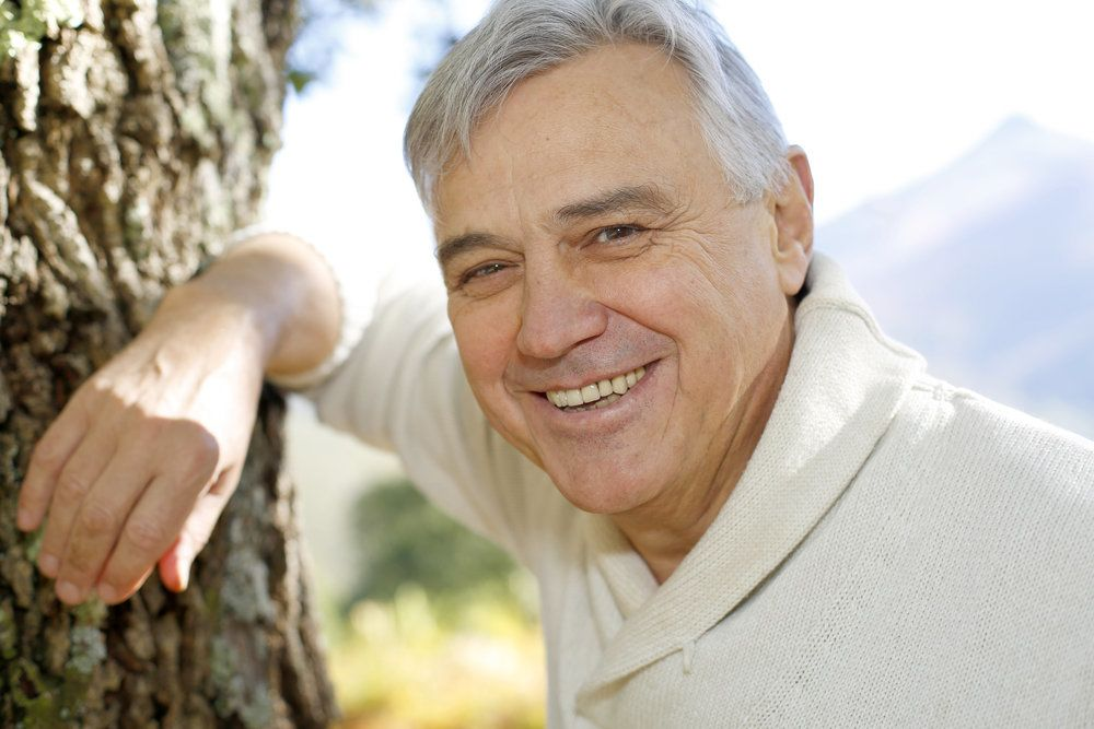 Older gentleman smiling to show a full set of attractive teeth