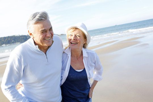 Older couple on beach laughing