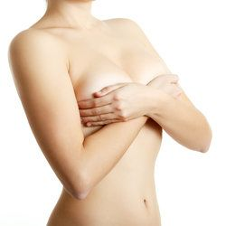 A topless woman faces to her left, holding her arms across her chest and cupping both of her breasts.