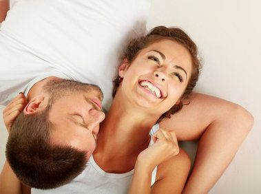 A young couple smiling and laughing together in bed - her sex drive reignited with the o-shot