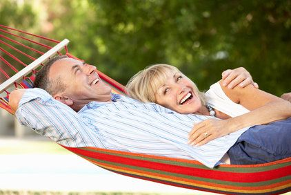 Older couple lying in a hammock and laughing
