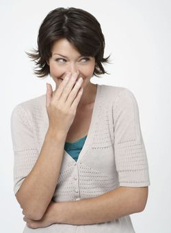 A laughing woman covering mouth