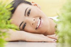 Happy looking woman lying in field with cheek resting on back of hand