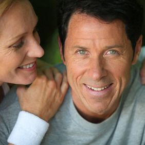 A middle-aged man and woman smiling