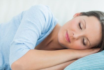 Relaxed woman resting cheek on top of folded arms.