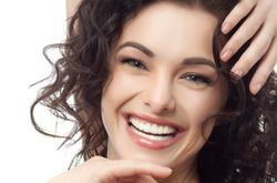 Young woman with dark hair smiling and looking quite happy