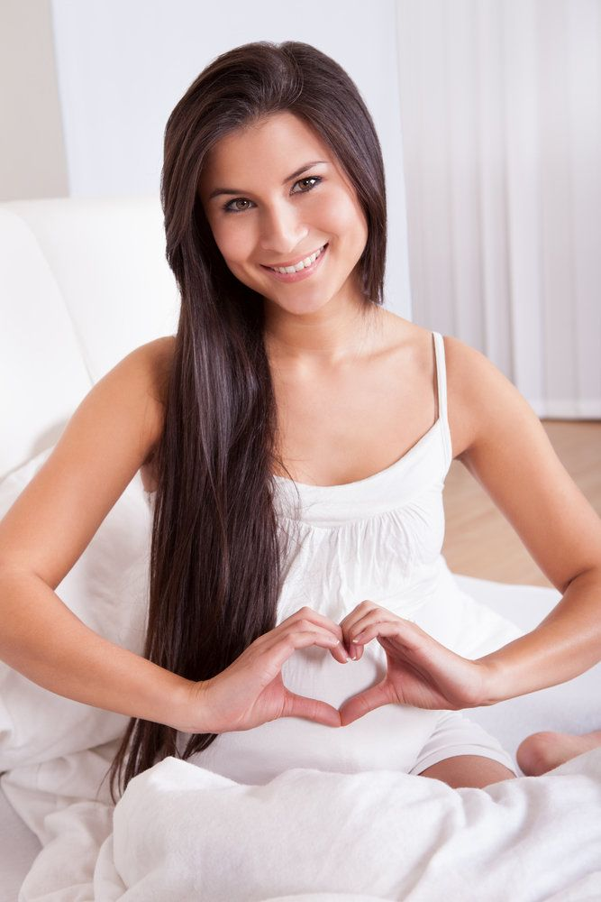 A woman making a heart shape with her hands in front of her belly, symbolizing fertility