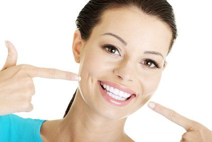 Broadly smiling woman pointing to her bright, white teeth
