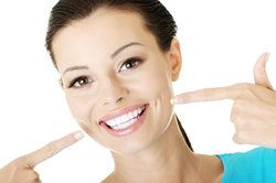 Attractive woman pointing to straight, very white teeth