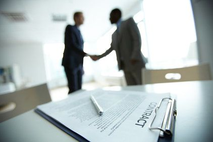 A contract on a table with two men shaking hands in the background